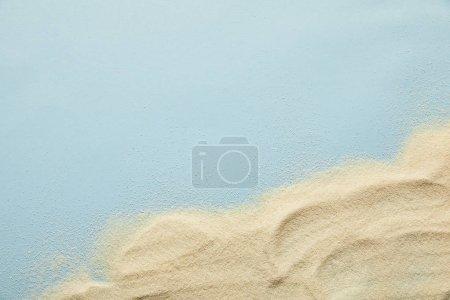 Draufsicht auf strukturierten goldenen Sand auf blauem Hintergrund mit Kopierraum