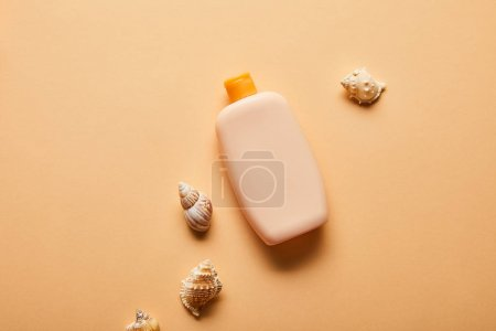 Photo for Top view of sunscreen in bottle near seashells on beige background - Royalty Free Image