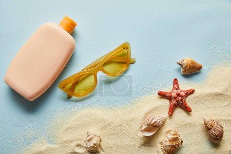 Photo pour Vue supérieure de la protection solaire dans la bouteille près des coquillages, des étoiles de mer, du sable et des lunettes de soleil sur le fond bleu - image libre de droit