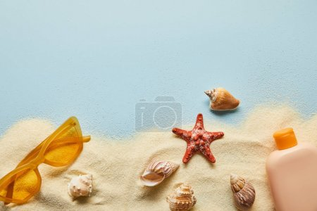 Photo for Top view of sunscreen lotion in bottle near sunglasses on blue background with sand and seashells - Royalty Free Image