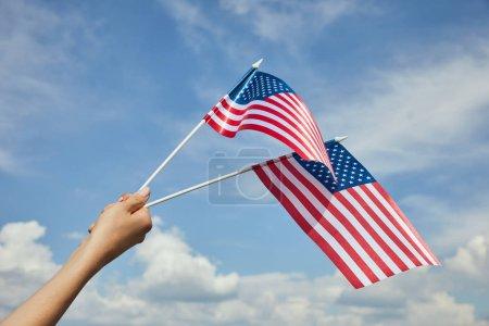 Vista recortada de una mujer sosteniendo banderas americanas en la mano sobre fondo azul del cielo