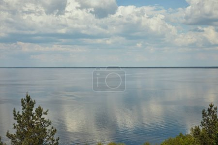 Photo for Peaceful landscape with green leafy trees, and horizon between river and blue sky - Royalty Free Image