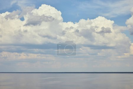 Landscape with river and white clouds on blue sky