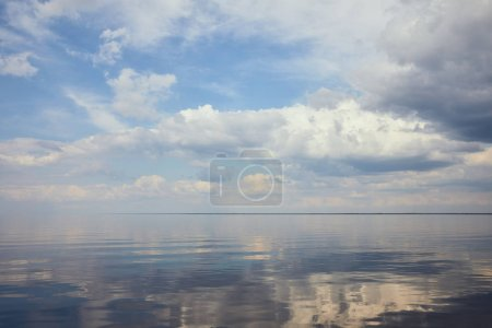 Calm pond and light blue sky with white clouds