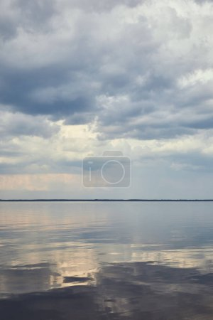 Blue peaceful sky with white clouds over river
