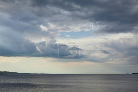Photo pour Overcast weather with clouds on blue sky over river coastline - image libre de droit