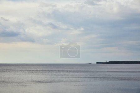 White clouds on blue sky over river with forest on coast