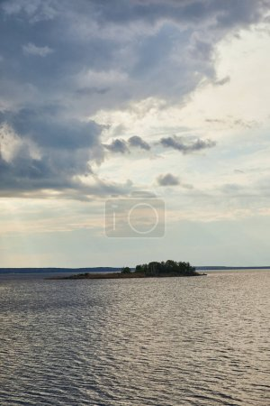 Photo for Blue clouds on light blue sky over river with forest on island - Royalty Free Image