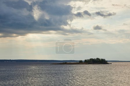 Photo for Blue clouds on sunlight sky over river with forest on island - Royalty Free Image