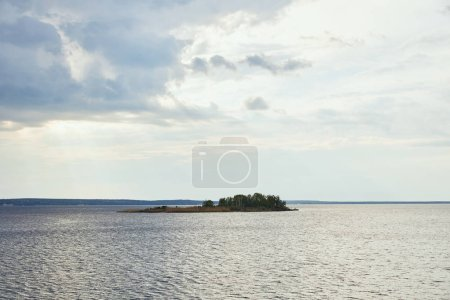 Photo for Sunny weather with blue clouds on white sky background upon small island with forest - Royalty Free Image