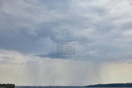 Photo for Overcast view of blue clouds and rain upon forest coast - Royalty Free Image