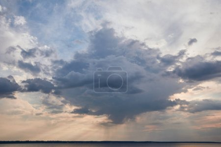 Photo for Dark cloud and sun rays on blue sky background - Royalty Free Image