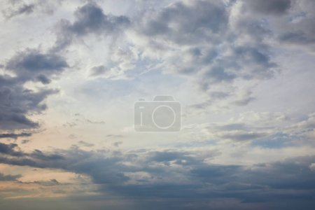 Photo for Blue clouds on grey sky background and sun rays - Royalty Free Image