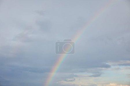 Photo pour Arc-en-ciel sur le fond bleu de ciel avec des nuages et la lumière du soleil - image libre de droit