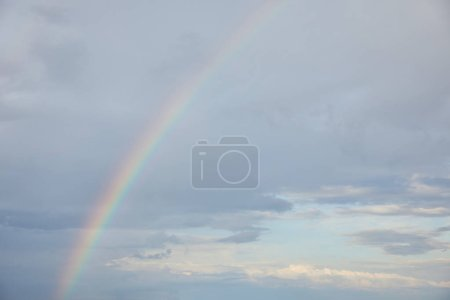 Photo for Rainbow on blue sky background with white clouds - Royalty Free Image