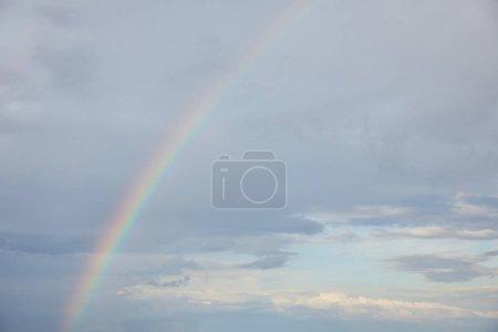 Foto de Rainbow on blue sky background with white clouds - Imagen libre de derechos