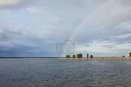 Photo for Landscape of blue sky, rainbow, river and coast with trees - Royalty Free Image