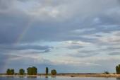 "Постер, картина, фотообои ""landscape of blue sunlight sky, rainbow, river and coast with trees"""
