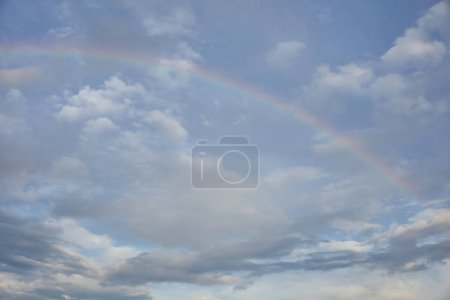 Photo pour Rainbow on blue sky background and white clouds - image libre de droit