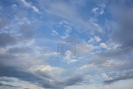 view of rainbow on blue sky background and blue clouds