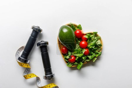 Photo for Top view of vegetables in heart-shaped bowl, measuring tape and dumbbells on white background - Royalty Free Image