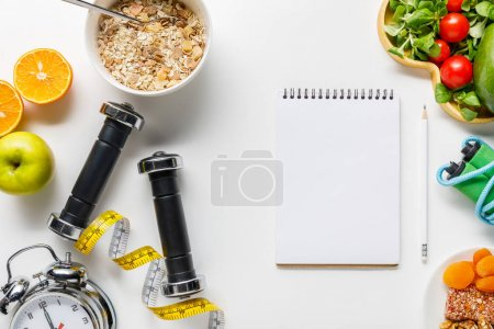 Photo for Top view of sport equipment, measuring tape, alarm clock and diet food near blank notebook on white background - Royalty Free Image