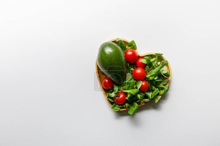 Photo for Top view of fresh green vegetables in heart shaped bowl on white background - Royalty Free Image