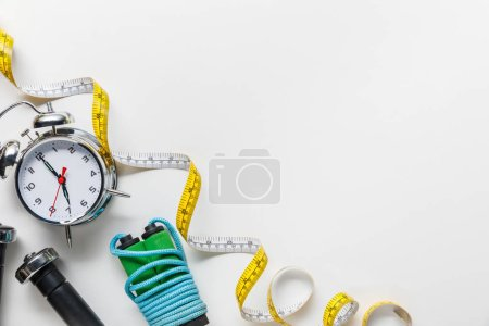 Photo for Top view of sport equipment, measuring tape, alarm clock on white background - Royalty Free Image
