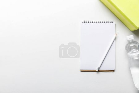 Photo for Top view of water in bottle and blank notebook with pencil near box on white background - Royalty Free Image