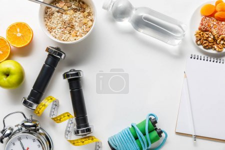 Photo pour Top view of dumbbells, skipping rope, measuring tape, alarm clock and breakfast cereal with fruits near water and notebook on white background - image libre de droit