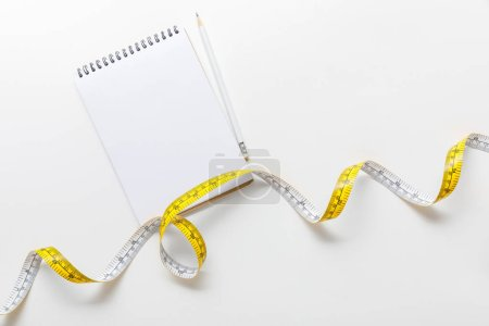 Photo for Top view of measuring tape, blank notebook with pencil on white background - Royalty Free Image