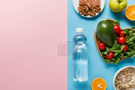 Photo for Top view of bottle with water and diet food on blue and pink background - Royalty Free Image