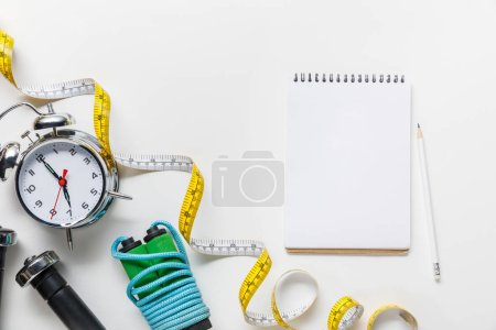 Photo for Top view of sport equipment, measuring tape, alarm clock near blank notebook on white background - Royalty Free Image