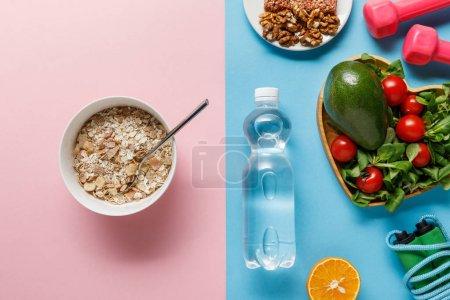 Photo pour Vue supérieure de la bouteille avec l'eau, nourriture de régime, équipement de sport sur le fond bleu et rose - image libre de droit
