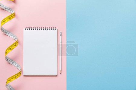 Foto de Vista superior de la cinta de medición y cuaderno en blanco con lápiz sobre fondo azul y rosa - Imagen libre de derechos