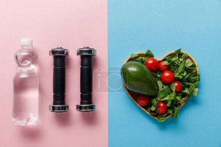 Photo for Top view of green salad in heart-shaped bowl near dumbbells and water on blue and pink background - Royalty Free Image