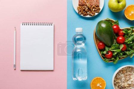 Photo pour Vue supérieure de la bouteille avec l'eau et la nourriture de régime près du cahier blanc sur le fond bleu et rose - image libre de droit