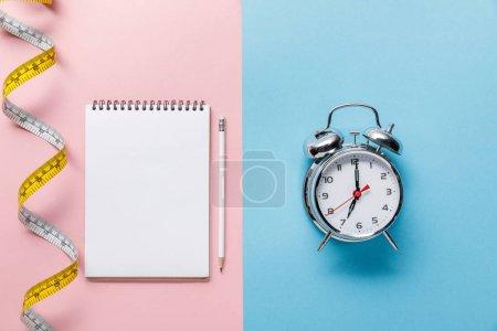Photo pour Vue supérieure du ruban à mesurer et du cahier blanc avec le crayon sur le bleu et le réveil sur le fond rose - image libre de droit