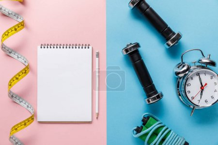 Photo for Top view of measuring tape and blank notebook with pencil on blue and alarm clock near skipping rope and dumbbells on pink background - Royalty Free Image
