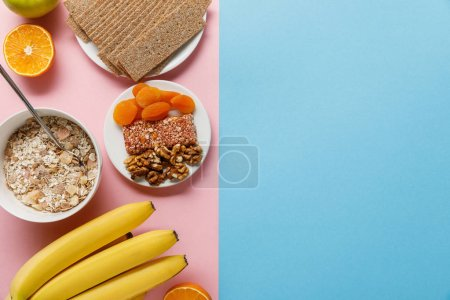 Photo for Top view of fresh fruits, crispbread and breakfast cereal on blue and pink background with copy space - Royalty Free Image