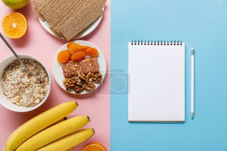 Photo for Top view of fresh fruits, crispbread and breakfast cereal on pink and blank notebook on blue background - Royalty Free Image