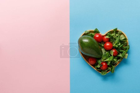 Photo for Top view of fresh green vegetable salad in heart shaped bowl on pink and blue background - Royalty Free Image