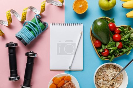 Photo for Top view of fresh diet food near sport equipment and measuring tape around blank notebook on pink and blue background - Royalty Free Image