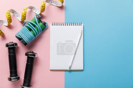Photo for Top view of notebook, dumbbells, skipping rope and measuring tape on blue and pink background - Royalty Free Image