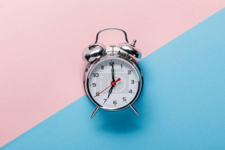 top view of classic silver alarm clock on pink and blue background
