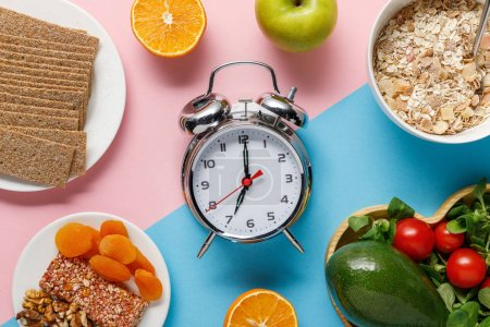 Photo for Top view of silver alarm clock with tasty diet food on blue and pink background - Royalty Free Image