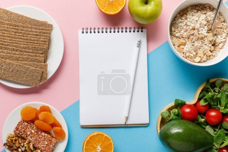 Photo for Top view of empty notebook and pencil with tasty diet food on blue and pink background - Royalty Free Image