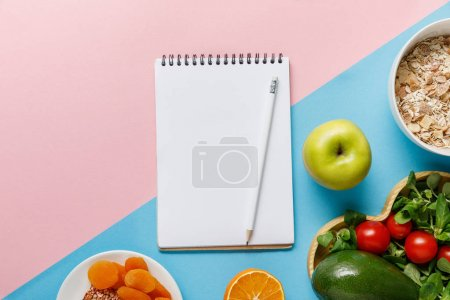 Photo for Top view of empty notebook and pencil with delicious diet food on blue and pink background - Royalty Free Image