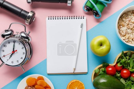 Photo for Top view of empty notebook and pencil with delicious diet food and sport equipment on blue and pink background - Royalty Free Image