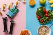 """Постер, картина, фотообои """"верхний вид вкусной диетической еды и спортивного оборудования с измерительной лентой на синем и розовом фоне"""""""